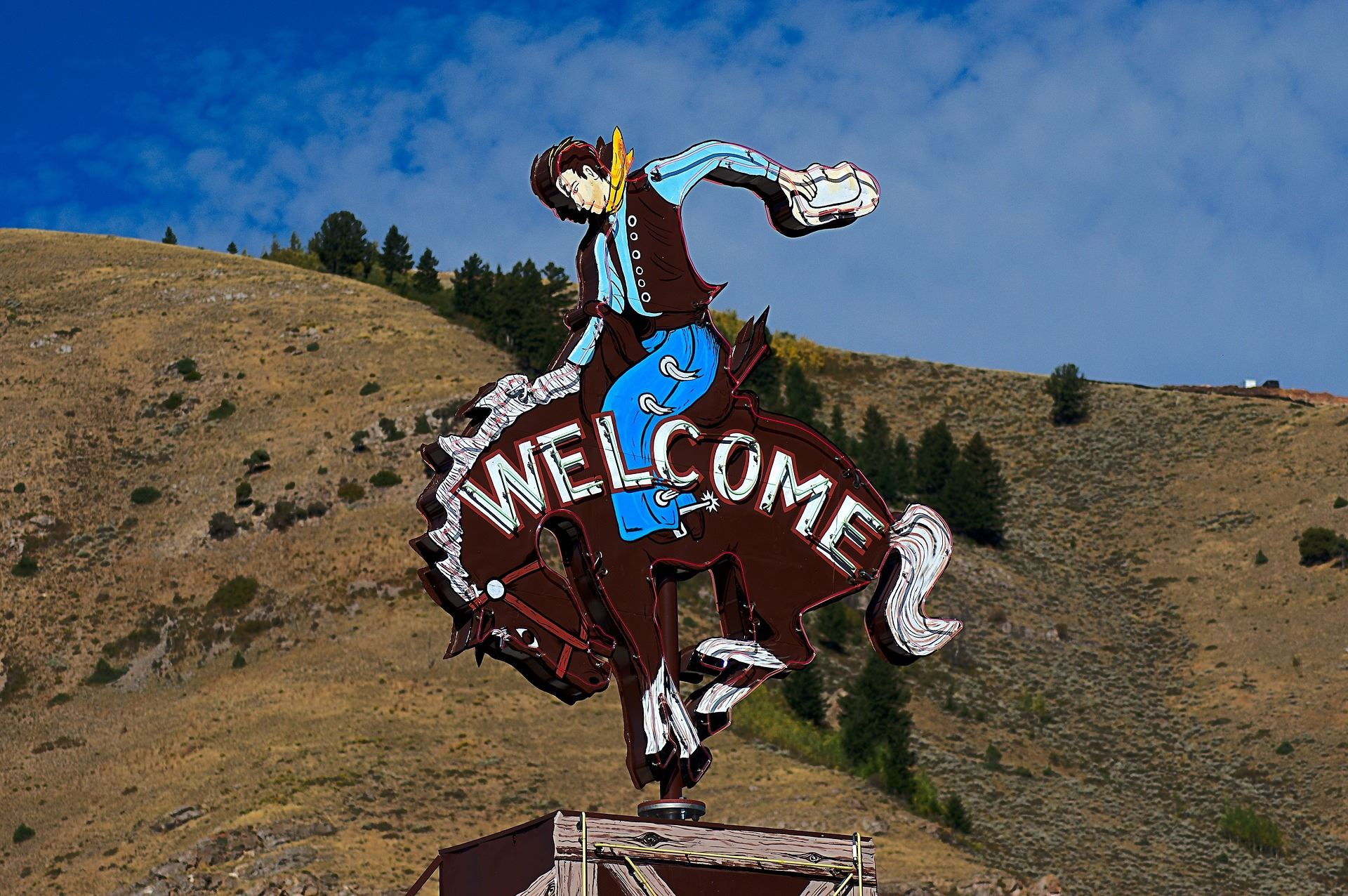 "Million Dollar Cowboy Bar sign of a cowboy riding a bucking horse that says ""Welcome"""